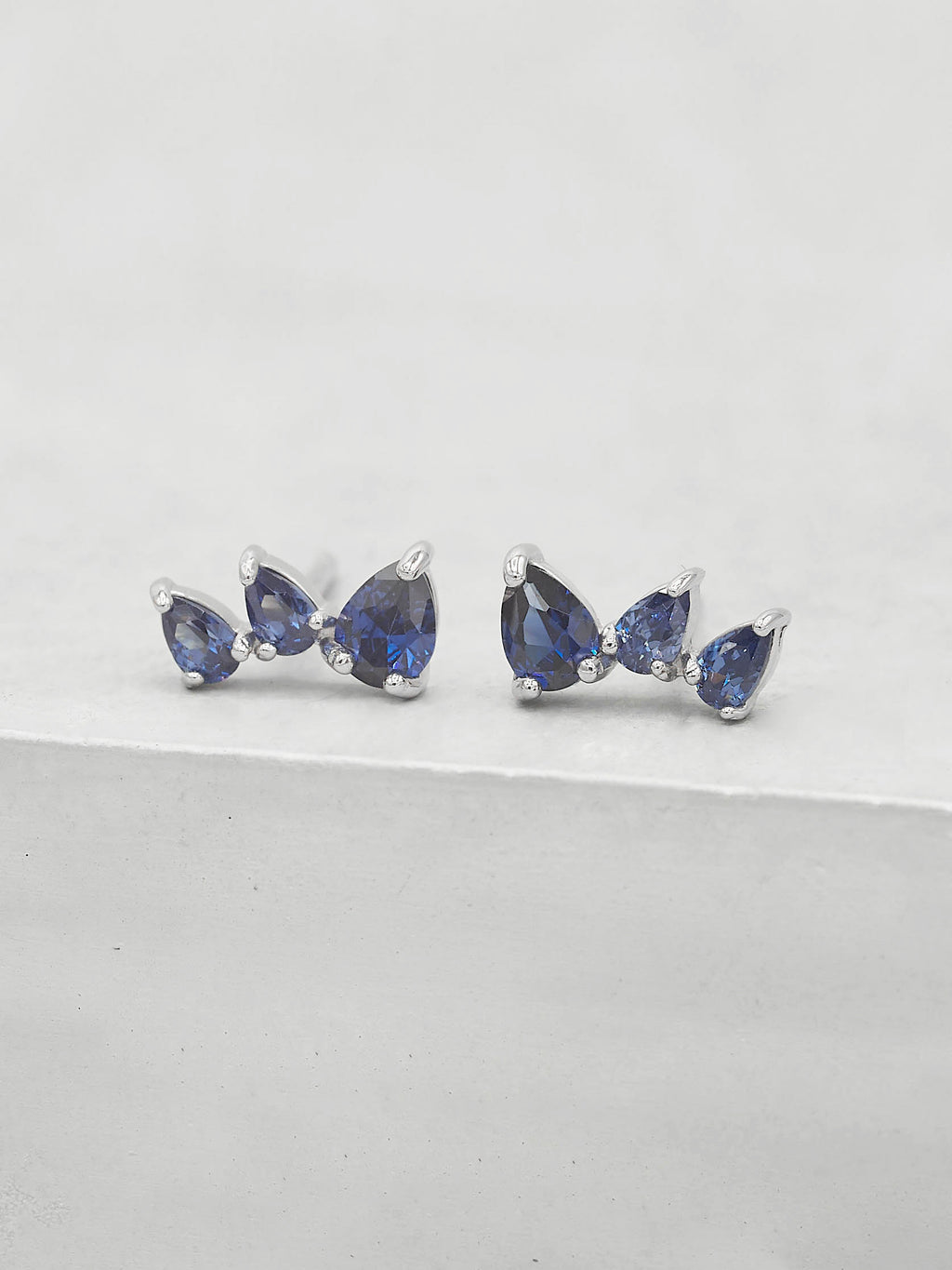 Rhodium Plated  3 Stones Blue Sapphire Pear Shape Cubic Zirconia CZ Stud Earrings by The Faint Hearted jewelry