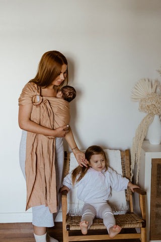 Chelsea and her daughters in the playroom. Chelsea wears a Chekoh Baby Ring Sling Carrier in Terracotta