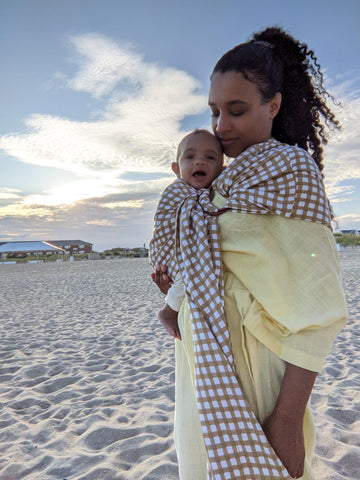 Immy on a beach with her little one, enjoying hands free snuggles with a Chekoh Ring Sling Carrier