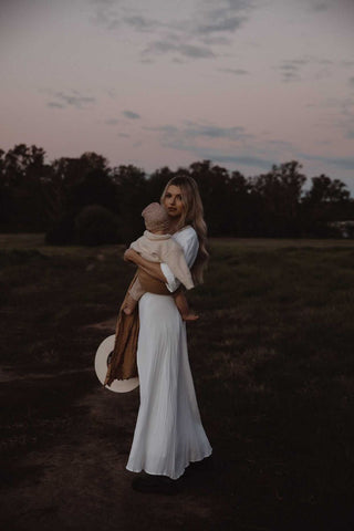 Mady Lee baby wearing in a field in a Chekoh Ring Sling Carrier in Camel colour