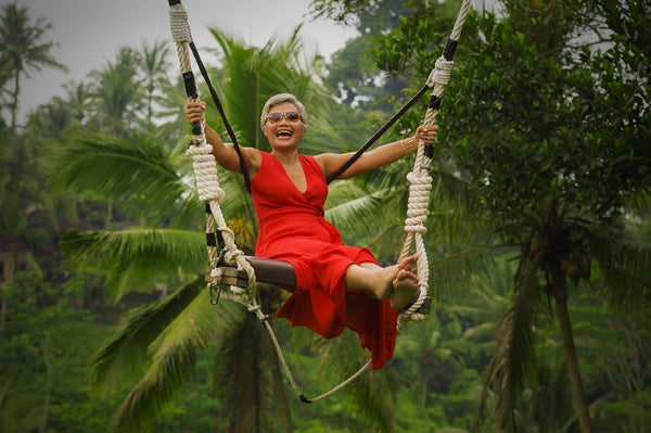mature woman laughing on swing