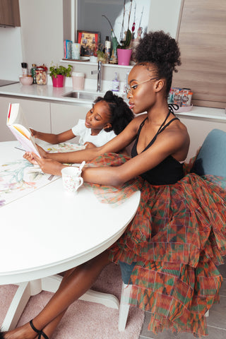 Little girl reading at the table together with Black Barbie in a Daolondon Kente Skir