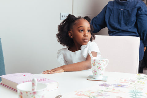 Black girl sitting at a table