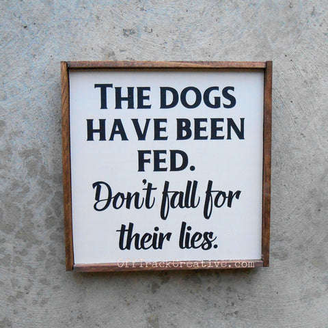 Painted wood sign that says The Dogs have been fed. Don't fall for their lies.
