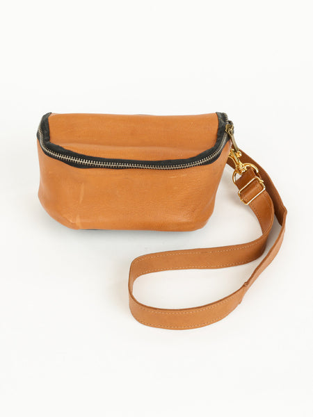 Tan leather fanny pack with double zipper closure and adjustable strap. The Lore by deux mains. Front view.
