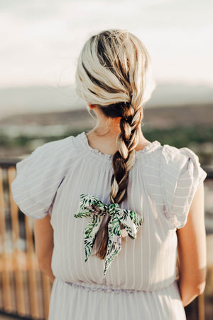 Aloe Hair tie, worn at the end of a braided pony tail tied in a bow. Model has brown hair with blonde highlights.