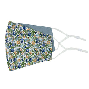 Alpine Blum and Dusty Reversible Face Mask. Outside is white background with small blue and yellow flowers, small green leaves throughout. Inside is solid dusty blue textured fabric. White adjustable straps to loop over ears.