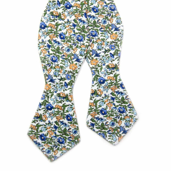 Alpine Blum Self Tie Bow Tie. White background with small blue and yellow flowers, small green leaves throughout.