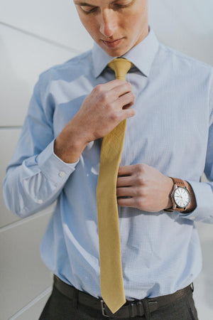 Amber tie worn with a light blue shirt and black pants.