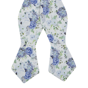Arctic Ice Self Tie Bow Tie. White background with dusty blue and navy blue flowers and succulents with green leaves.
