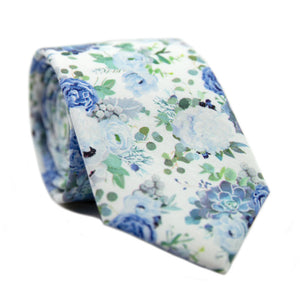 Arctic Ice Skinny Tie. White background with dusty blue and navy blue flowers and succulents with green leaves.