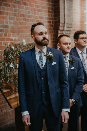 Atlanta tie worn by three groomsmen at a wedding with white shirts and navy blue suits.