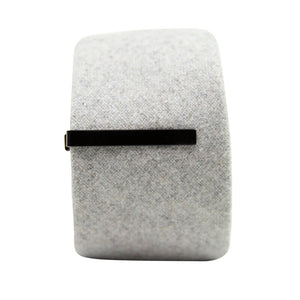 Solid black metal tie bar clipped onto a gray textured wool tie that is rolled up.