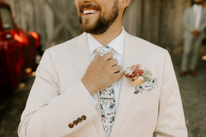 Blue bloom tie worn with a white shirt and light tan suit.