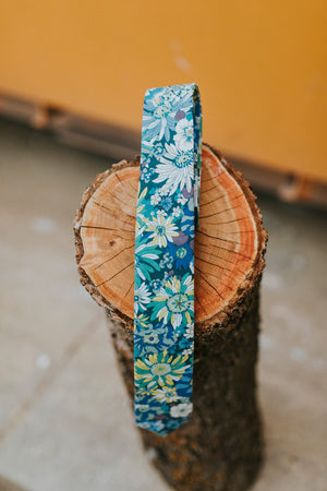 Blue Haven tie sitting on top of a cut log.