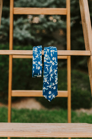 Blue Marlin tie hanging over a wooden ladder.