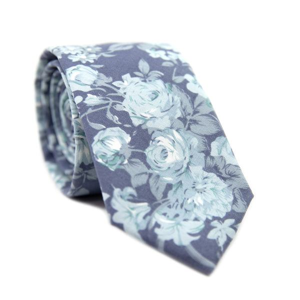 Blue Tropic Skinny Tie. Dusty blue background with light blue leaves and flowers, some turquoise accents throughout.