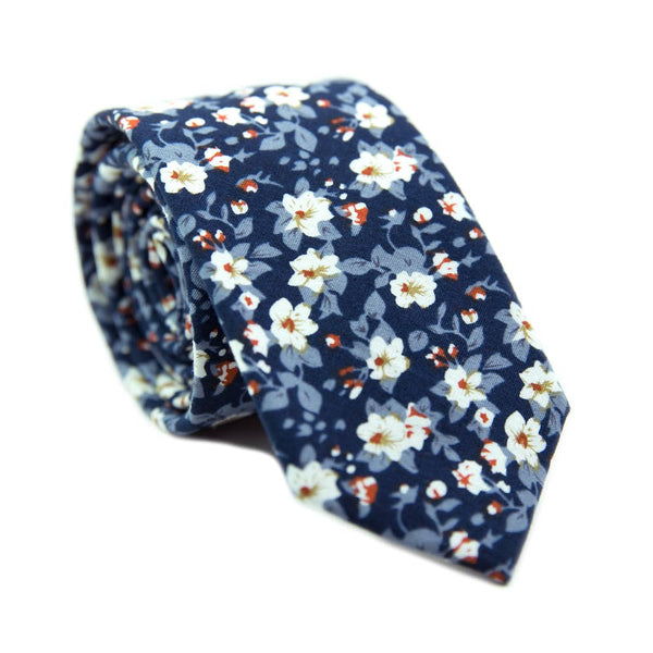Blueberry Bliss skinny tie. Navy background, light blue leaves, and small white flowers with a little red center.