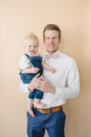 Blush Pre-Tied Bow Ties worn by dad and son wearing white shirts and blue pants.