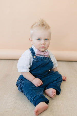 Blush Pre-Tied Bow Tie worn by baby with white shirt and blue denim overalls.