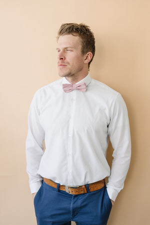 Blush Pre-Tied bow tie worn with a white shirt, brown belt and blue pants.