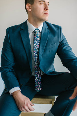 Botanical tie worn with a white shirt and blue suit.