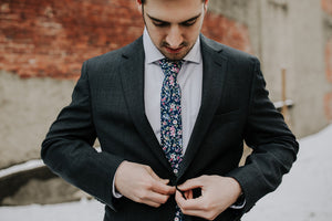 Botanical tie worn with a white shirt and black suit jacket.