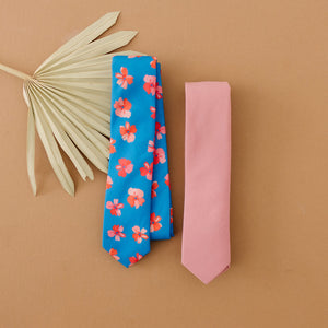 Bubblegum tie laying flat on a table next to another floral tie.