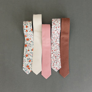 Five skinny ties laying flat next to one another.