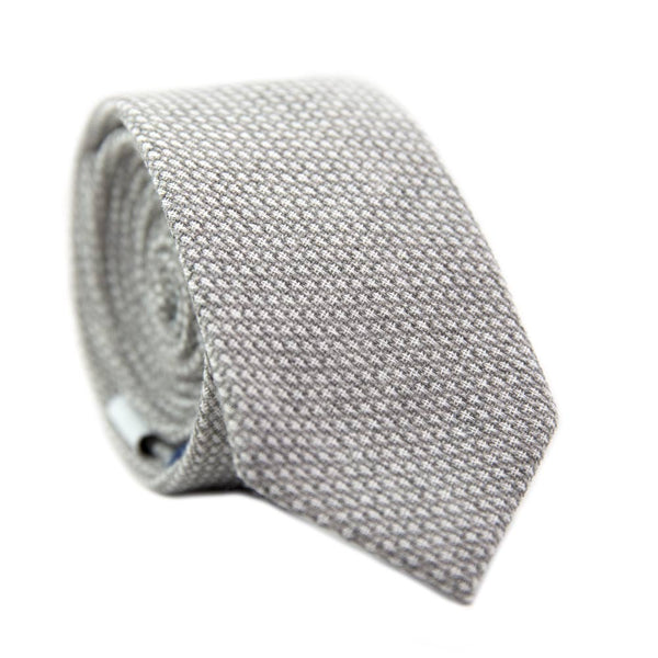 Calm Skinny Tie. Textured gray fabric with small textures of white throughout.