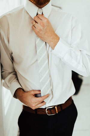 Camarillo tie worn with a white shirt, brown belt and black pants.