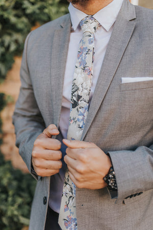 Carnation tie worn with a white shirt and gray suit jacket and a solid white pocket square.