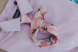 Cherry Blossom tie laying on a pink shirt.
