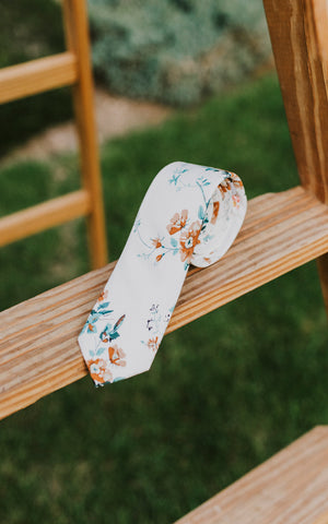 Copper Blooms tie rolled up and sitting on a wooden ladder.