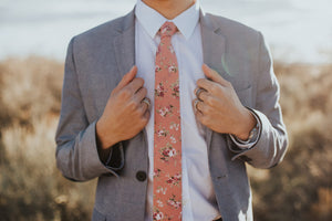 Desire tie worn with a white shirt and gray suit jacket.