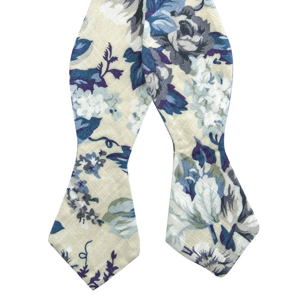 Dreamy Fields Self Tie Bow Tie. Cream background with dusty blue, white and gray flowers with navy blue and purple leaves.