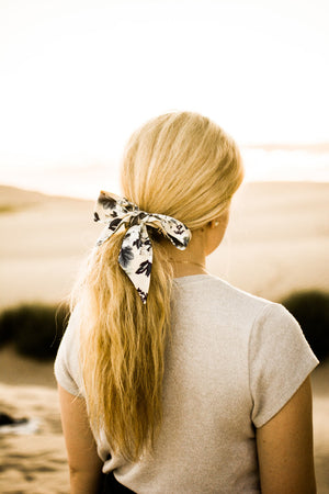 Dreamy Fields hair tie worn tied in a bow around a ponytail. Model has blonde hair.