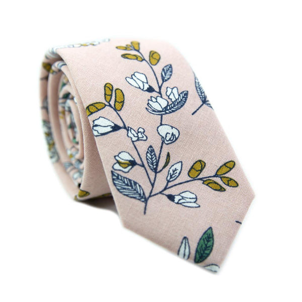 Dusty Lily Skinny Tie. Light pink background with white and green leaves and flowers, black stems, and some orange accents.