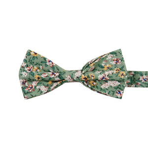 Faded Jade Pre-Tied Bow Tie. Sage background with white, blush and yellow flowers with blue flower centers, dark sage leaves.