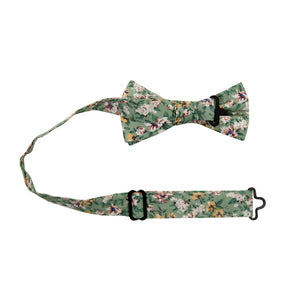 Faded Jade Pre-Tied Bow Tie with adjustable neck strap. Sage background with white, blush and yellow flowers with blue flower centers, dark sage leaves.