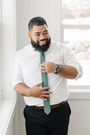 Forest tie worn with a white shirt and black pants.