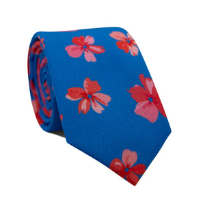Freely Grown Skinny Tie. Royal blue background with pink and red Hawaiian flowers throughout.
