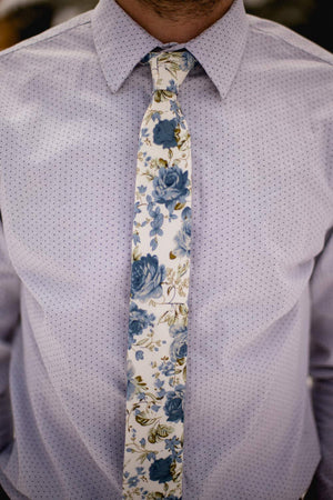 Frisco tie worn with a shirt that is light gray and has small black dots all over it.