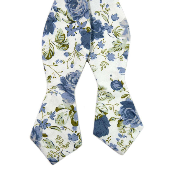 Frisco Self Tie Bow Tie. White background with small and medium size light blue flowers and sage green leaves.