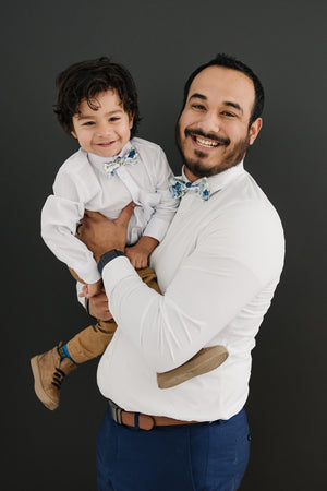 Frisco pre-tied bow ties worn by father and son wearing white long sleeve shirts.