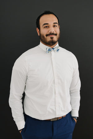Frisco pre-tied bow tie worn with a white shirt, brown belt and blue pants.