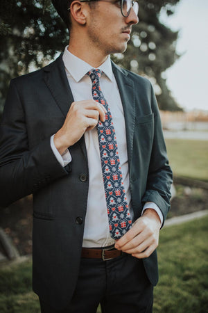 Gifted tie worn with a white shirt, brown belt and navy blue suit.