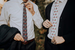 Gifted tie worn with a white shirt and navy pants next to another model wearing a different holiday themed tie.