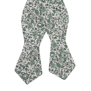 Hidden Garden Self Tie Bow Tie. White background with sage green flowers and leaves with black vines.