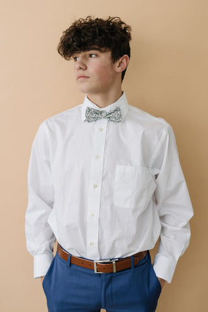 Hidden Garden pre-tied bow tie worn with a long sleeve white shirt, brown belt and blue pants.